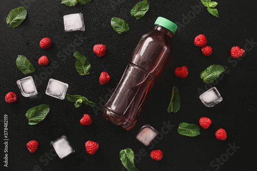 Fototapeta Bottle of fresh  tea, mint, ice cubes and raspberry on dark background obraz