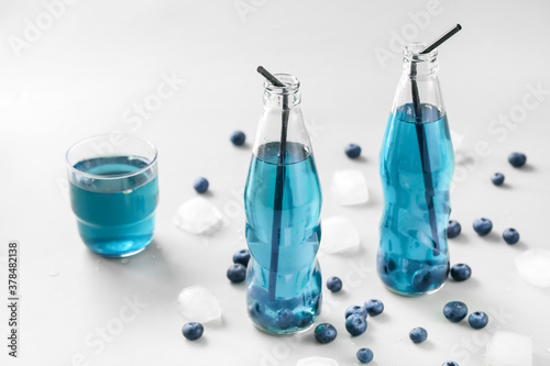 Fototapeta Bottles of fresh blueberry ice tea on light background obraz