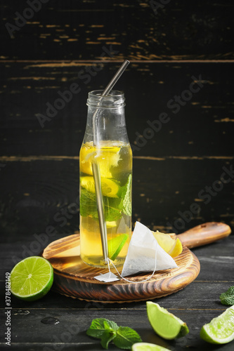 Fototapeta Bottle of fresh ice tea on dark background obraz