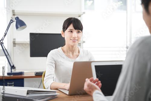 Obraz カジュアルなオフィスで会話する日本人デザイナーの男女 - fototapety do salonu