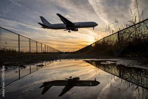 Fototapeta 夕暮れの飛行機 到着便 水溜まりリフレクション obraz