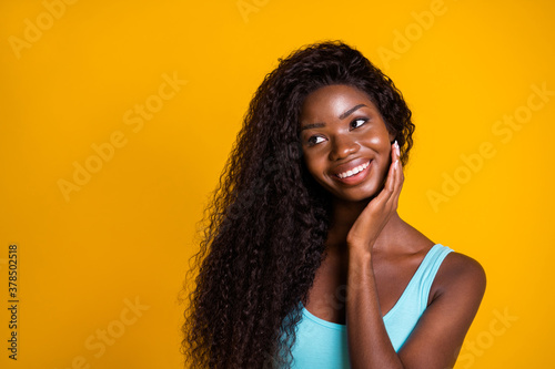 Photo portrait of pretty african american woman looking to side thinking touching face with hand isolated on vivid yellow colored background