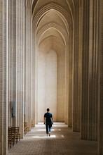 Young Man Walking Along Cloister, Grundtvigs Church, Copenhagen, Denmark