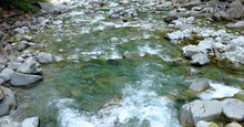 An Image Of A River With Clear Water Tumbling Over River Washed Stones