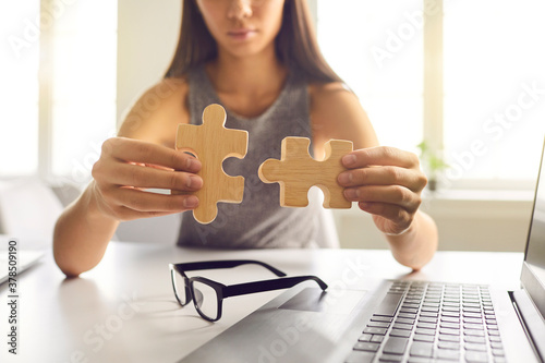 Close-up of businesswoman joining two pieces of jigsaw puzzle as metaphor for finding solution