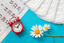 Alarm Clock, Feminine Pads And Calendar On A Blue Background, The Concept Of Monthly, Critical Days, Intimate Hygiene And Women's Health Care