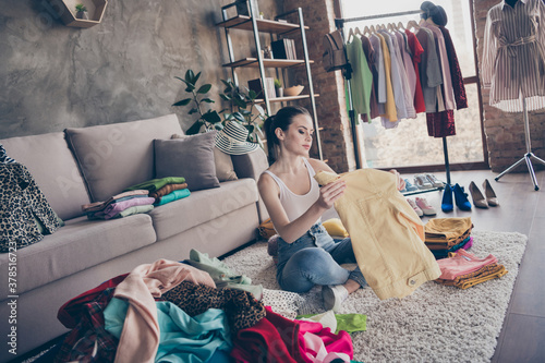 Obraz Full body focused girl house wife prepare for garage sale auction look pack her used dressing clothes pile stack sit floor carpet legs crossed folded in house indoors - fototapety do salonu