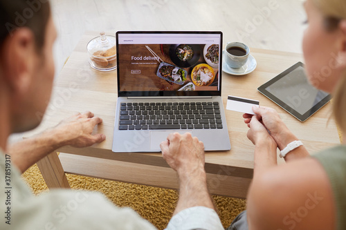 Obraz na plátně Image of laptop with food delivery site on the screen with young couple paying f