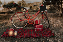 Red Vintage Bicycle With Its Basket Filled With Christmas Ornaments And A Picnic Blanket In Park