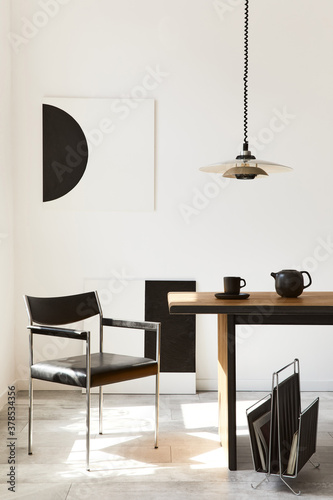 Fototapeta Stylish dining room interior with design wooden family table, black chairs, teapot with mug, mock up art paintings on the wall and elegant accessories in modern home decor. Template. obraz