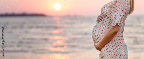 unrecognazible pregnant woman on the coast sunset. The concept of expectation of a child calm pacification silence. Gentle tones of tenderness. Place for text. belly close-up.