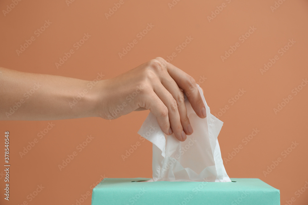 Fototapeta Woman taking paper tissue from box on light brown background, closeup