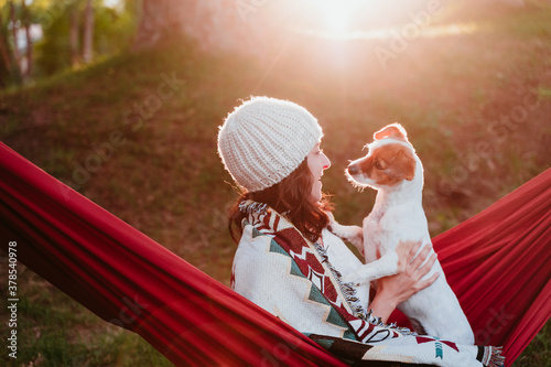 young woman relaxing with her dog in orange hammock. Covering with blanket. Camping outdoors. autumn season at sunset