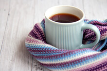 Blue Cup Of Hot Tea Is Wrapped In A Warm Striped Multi-colored Scarf. Autumn Background With Copy Space