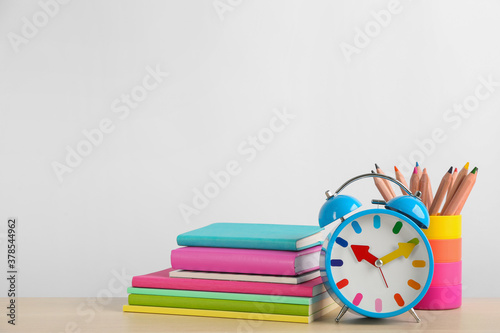Fototapeta Different school stationery and alarm clock on table against white background, space for text. Back to school obraz