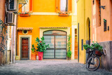 Fototapeta Uliczki - Old cozy street in Trastevere, Rome, Italy with a bicycle and yellow house.