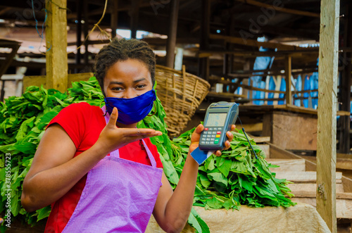 Fotografía a young beautiful african market woman wearing face mask to prevent herself from the society holding a pos machine