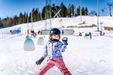 Young Happy Skier Girl Throwing Snowballs In Snowball Fight. Young Skier Having Fun On Ski Slope, Bialka Tatrzanska, Tatry, Poland