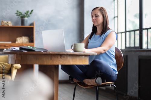 Fototapeta Beautiful relaxing businesswoman sitting near table in lotus pose working on laptop obraz