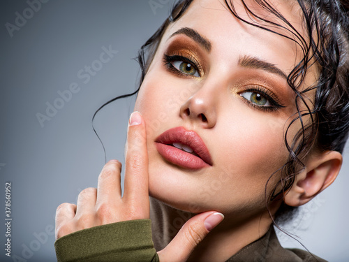 Closeup portrait of a beautiful young fashion woman with brown makeup posing at studio.