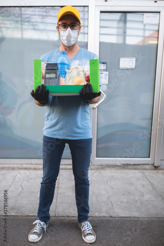 Fototapeta Delivery guy with protective mask holding box / bag with groceries and POS for contactless payment. obraz