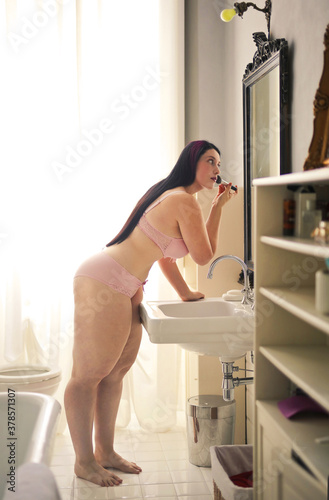 Tablou Canvas beautiful curvy girl in lingerie in the bathroom in front of the mirror