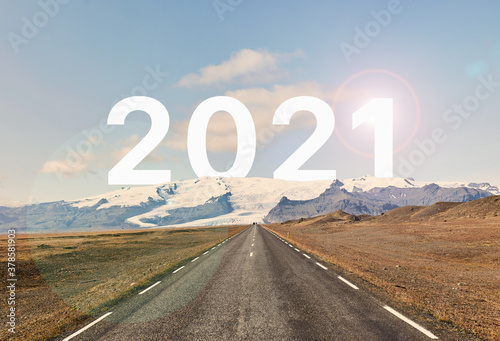 Fototapeta The word 2021 is written behind a glacier and an empty asphalt road against a golden sunset and beautiful blue sky. The year 2021 is written behind the glacier. obraz