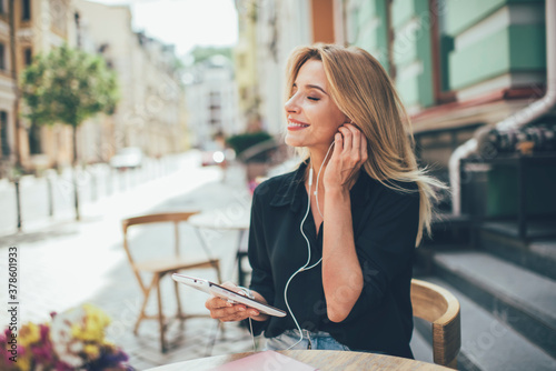 Photo Cheerful woman with closed eyes enjoying positive audio novel from digital table