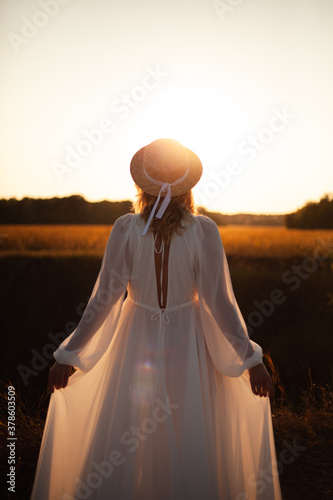 Happy woman standing with her back on sunset in nature . Woman in a long white dress with a hat on her head