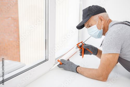 Fototapeta Worker in medical mask use silicone tube gun for repairing and installing window obraz