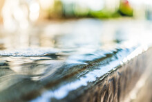 Detail Macro Abstract Close Up Of Golden Water Fountain Surface In Park With Bokeh
