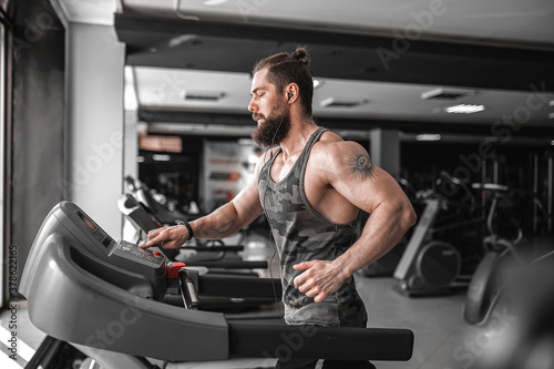 Adult strong bearded man running on treadmill in gym.
