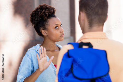Fototapeta Young african american woman gesturing stop and rejecting man obraz