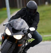 Handsome Motorcyclist In Black Riding His Super Sport Motorcycle.