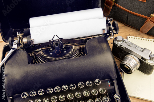 Photo an old 1940s black portable typewriter with a 35 mm film camera and a notebook s