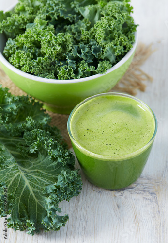 kale juice in a glass on white surface