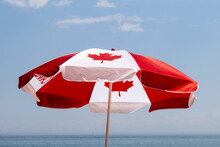 A Canadian Maple Leaf Flag Umbrella With The Horizon In The Distance Celebrating Canada Day On The Beach
