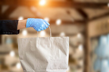Small Business And Service Concept With Young Woman Wearing Blue Gloves Filed Paper Bag With Take Away Drink In Cafe