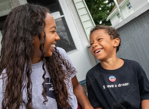 Valokuva Young African AMerican boy wearing an Ivoted sticker laughing with his multi-rac
