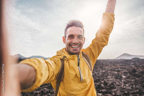Foto Handsome man taking a selfie climbing a rock