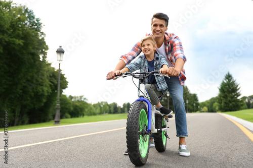 Fototapeta Dad teaching son to ride bicycle outdoors obraz
