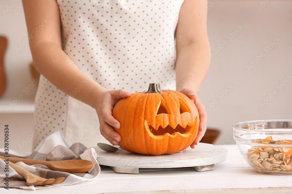 Fototapeta Woman carving pumpkin for Halloween at table