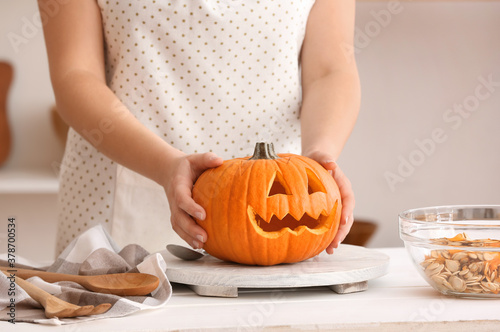 Woman carving pumpkin for Halloween at table Fototapet