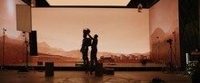 Behind The Scenes Shot Of Virtual Production Stage With Huge LED Screens, Cinematorgapher Shooting Mars Scene. Future Of Movie Production