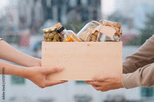 Fototapeta Volunteers with donation box with foodstuffs obraz
