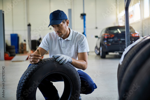 Obraz na plátně Mechanic measuring depth of car tires in auto repair shop.