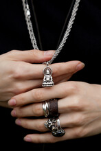 Hands Holding A Pendant With Buddha
