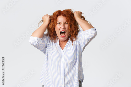 Fototapeta Angry and hateful middle-aged redhead woman looking outraged and bothered, grima