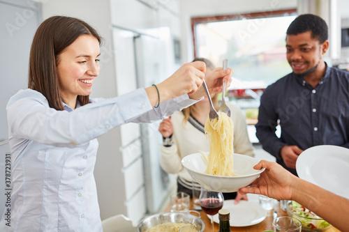 Foto Frau beim Spaghetti servieren bei Mahlzeit mit Freunden