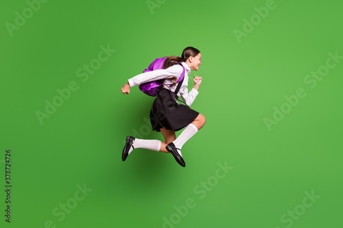 Photo portrait of brunette girl with pigtails running to school jumping up with Wallpaper Mural